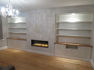 Alcove shelving and cabinets on either side of chimney breast with artificial fire